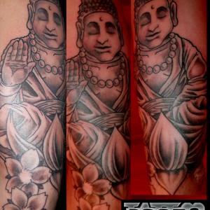 Tatuaje Buda sentado en flor de loto con flores de almendro en sombras, brazo chica