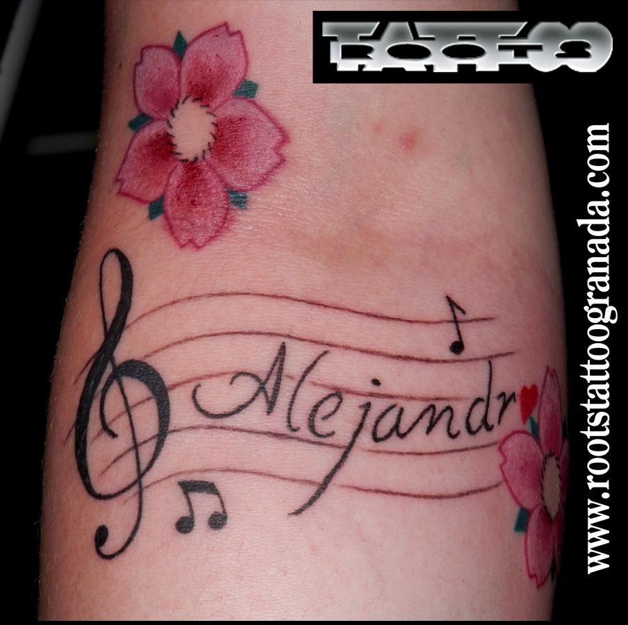 Tatuaje nombre con clave de sol, pentagrama, flores de cerezo y notas musicales