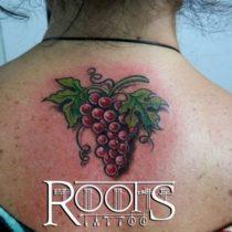 Tatuaje de racimo de uvas moradas con hojas de parra