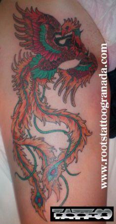 Tatuaje fenix muslo chica, colores vivos plumas largas