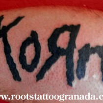 tatuaje logotipo korn, tinta plana, negro, letras, antebrazo, hombre, Serafín Rabé, Roots Tattoo Granada